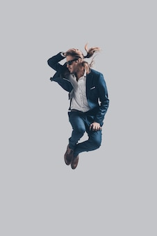 Sich wohl fühlen in seinem stil. hübscher junger mann in vollem anzug und sonnenbrille springen