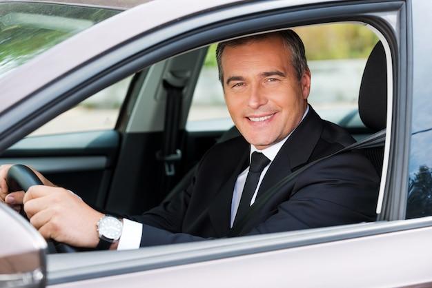 Sich wohlfühlen in seinem neuen auto. fröhlicher reifer mann in formeller kleidung, der auto fährt und lächelt