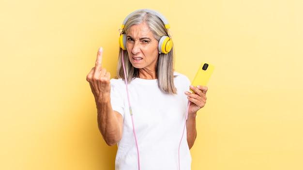 Sich wütend, genervt, rebellisch und aggressiv fühlen, mit dem mittelfinger schlagen, sich mit kopfhörern wehren