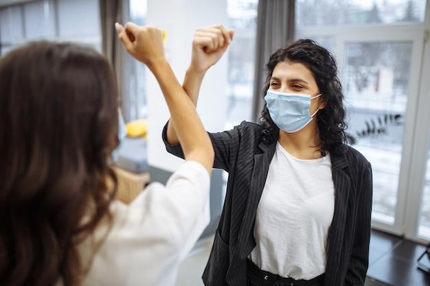 Sichere begrüßung von zwei geschäftsfrauen, die während der coronavirus-pandemie masken tragen.