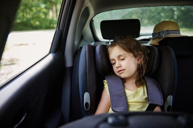 Sichere bewegung von kindern im auto. kleines mädchen schläft in einer sitzerhöhung im auto. kindersitz.
