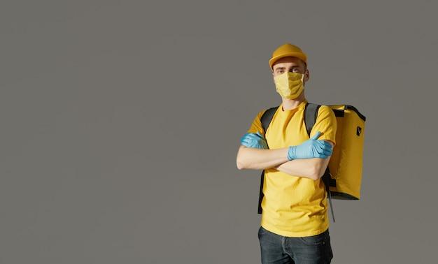 Sichere lebensmittellieferung. kurier in gelber uniform, schutzmaske und handschuhen liefert essen zum mitnehmen während der coronovirus-quarantäne. kopieren sie platz für text