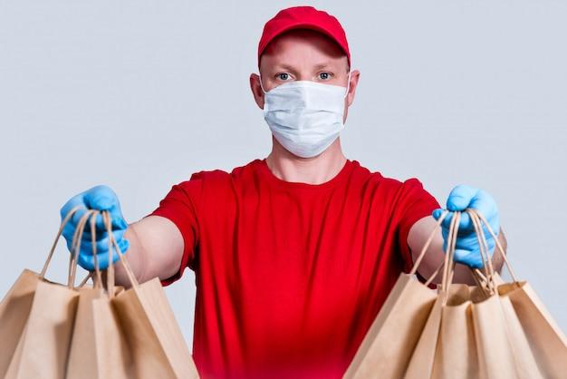 Sichere lieferung. ein kurier in roter uniform, schutzmaske und handschuhen hält einen großauftrag, viele papiertüten, kontaktlose liefernahrungsmittel in quarantäne. spende von freiwilligen. kein verlust.