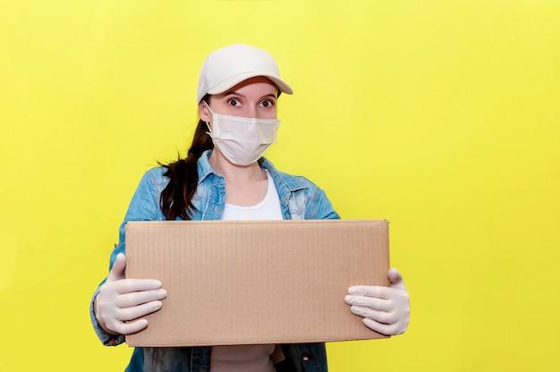Sichere lieferung. frau kurier in schutz gesichtsmaske und handschuhe mit karton. anti-coronavirus-konzept.
