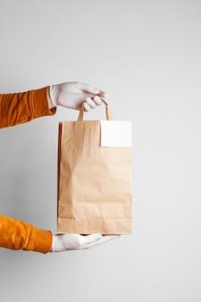 Sichere lieferung von lebensmitteln in einer basteltasche und einem pizzaboten zu hause auf einem weißen hintergrund