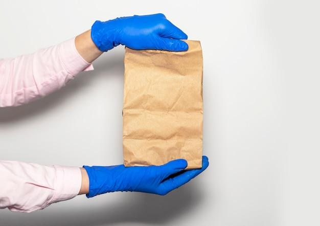 Sicheres lieferkonzept. basteln sie paket oder paket in händen des kuriers in schutzhandschuhen auf weißem hintergrund. sicherheit beim online-shopping.