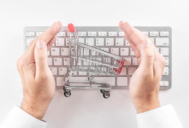 Sicheres online-shopping-konzept. einkaufswagen mit hand auf weiß geschützt