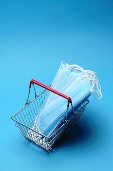 Sicheres und online-shopping im quarantäne-konzept. einkaufskorb mit medizinischer schutzmaske über blauem hintergrund
