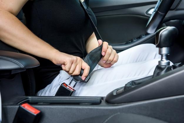 Sicherheit auf der straße. fahrerin, die den sicherheitsgurt im auto anschnallt