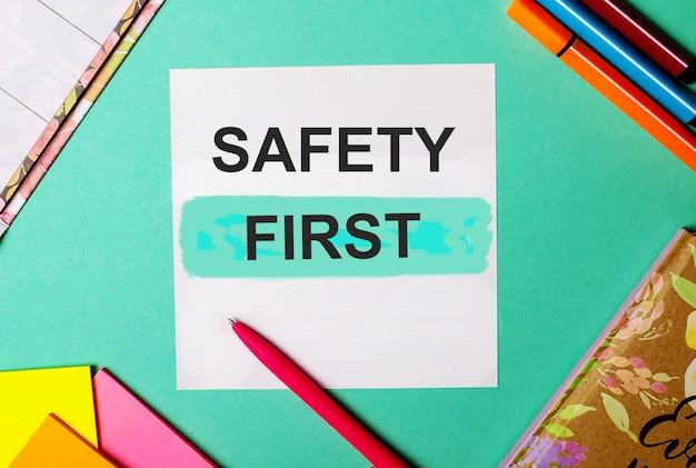 Sicherheit zuerst auf türkisfarbener oberfläche in der nähe von hellen aufklebern, notizblöcken und markern geschrieben