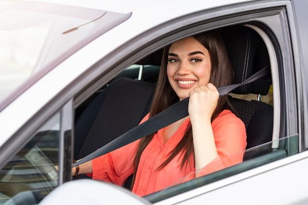 Sicherheit zuerst. schöne kaukasische dame, die autosicherheitsgurt festlegt.