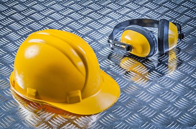 Sicherheits-ohrenschützer-schutzhelm auf geriffelter blechkonstruktion