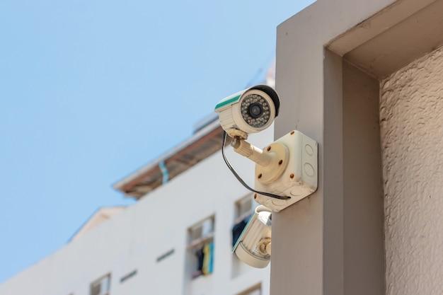 Sicherheits-überwachungskamera oder überwachungssystem im bürogebäude auf hintergrund des blauen himmels