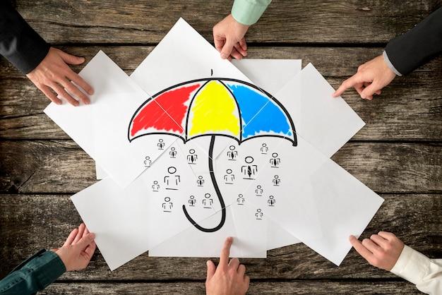 Sicherheits- und lebensversicherungskonzept - sechs hände, die einen bunten regenschirm zusammenbauen, der viele menschensymbole schützt, die auf weißbüchern gezeichnet sind.