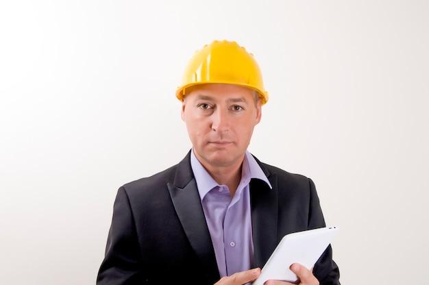 Sicherheitsarbeit. freundlicher ingenieur mit dem gelben sturzhelm unter verwendung seiner digitalen tablette