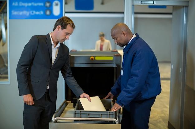 Sicherheitsbeamter des flughafens, der das passagierpaket überprüft