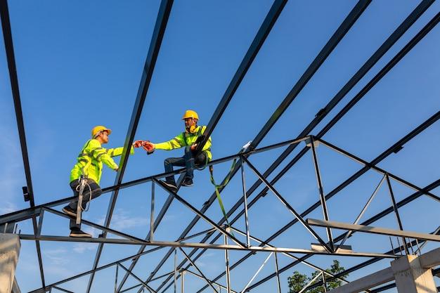 Sicherheitshöhenausrüstung auf der baustelle; asiatische arbeiter tragen sicherheitsausrüstung, um das dach zu installieren. absturzsicherungsvorrichtung für arbeiter mit haken für sicherheitsgurt.