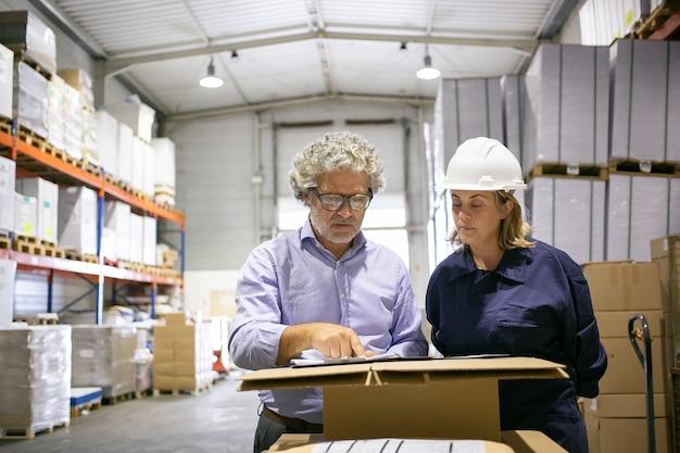 Sicherheitsinspektor berät weibliche logistikarbeiterin beim ausfüllen des formulars im lager. kopierraum, vorderansicht. arbeits- und inspektionskonzept