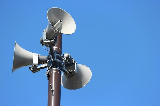 Sicherheitslautsprecher ragen für das warnen hoch oder kündigen mit klarem hintergrund des blauen himmels an