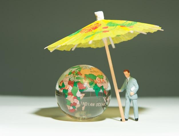 Sicherheitsmann hält regenschirm unter glaskugel