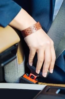 Sicherheitsmaßnahmen. schließen sie oben von einer weiblichen hand, die den sicherheitsgurt während des fahrens des autos befestigt