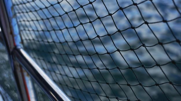 Sicherheitsnetz auf dem boot. seile auf dem boot. sicherheitsseile und blaues meer. wellen auf dem meer und sicherheitsnetz.