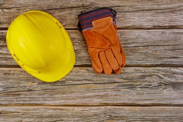 Sicherheitsschutzhandschuhe für den schutz der baustelle auf holzhintergrund