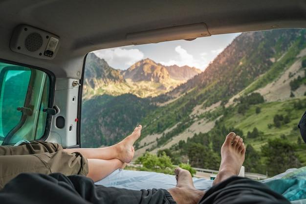 Sicht auf die beine eines romantischen paares in einem alten lieferwagen, der zusammen die erstaunliche landschaft genießt?