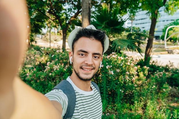 Sicht eines jungen kaukasischen reisenden, der ein selfie in einem park macht