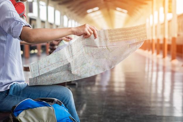 Side portrait eines jungen mannes reisenden sitzen mit karte wählen, wo zu reisen und tasche warten auf zug, vintage-ton-filter bewirkt