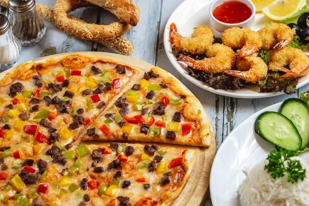 Side viiew fleischpizza mit rotem gelbem und grünem paprika fleischkäse und tempuragarnelen auf dem tisch