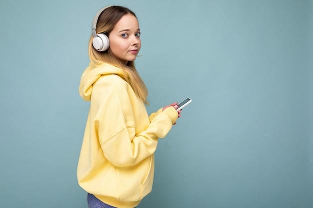 Sideprofile schöne ernste junge blonde frau mit gelbem stylischem hoodie isoliert auf blau