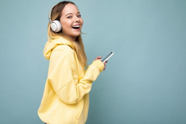 Sideptofile-foto einer schönen lachenden, glücklichen jungen frau, die ein stilvolles, lässiges outfit trägt, isoliert