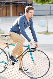 Sideview mann, der fahrrad draußen reitet