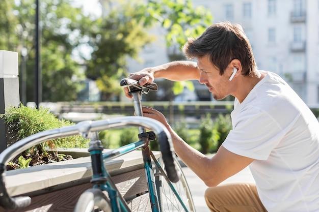 Sideview-mann, der sein fahrrad repariert