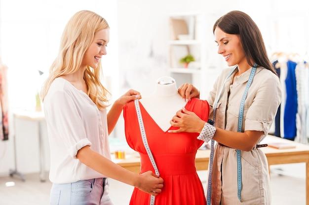 Sie achten auf details. zwei lächelnde junge frauen, die das kleid messen und anpassen, während sie in ihrer modewerkstatt stehen