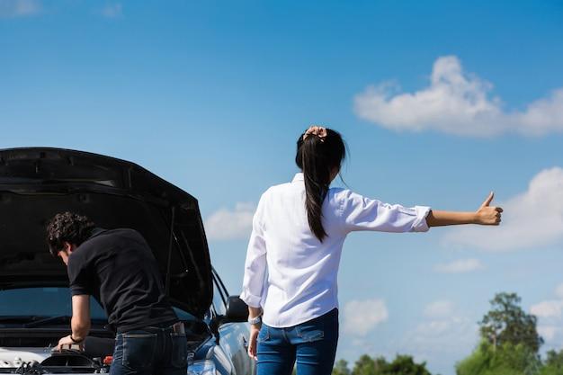 Sie beide paare broken auto auf der straße suche nach hilfe das auto kommt