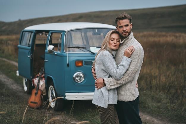 Sie bewachen. schönes junges paar, das umarmt und lächelt, während es nahe dem blauen retro-stil-minivan steht