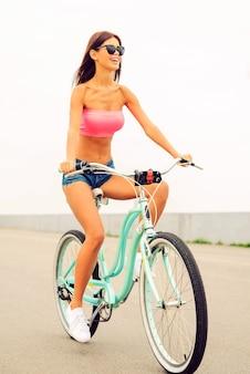Sie fährt ihr brandneues fahrrad. schöne junge lächelnde frau, die fahrrad entlang einer straße fährt