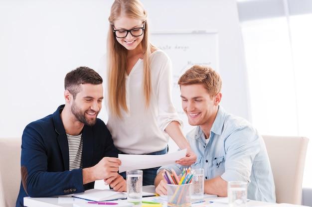 Sie haben kreative köpfe. drei selbstbewusste geschäftsleute in eleganter freizeitkleidung diskutieren etwas, während sie sich das dokument gemeinsam ansehen