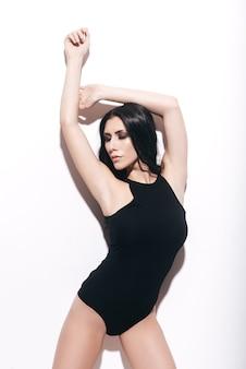 Sie hat perfekte kurven. attraktive junge frau im schwarzen badeanzug posiert vor weißem hintergrund und hält die augen geschlossen