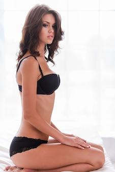Sie hat perfekte kurven. schöne junge frau mit braunen haaren in schwarzen dessous, die im bett sitzt und wegschaut
