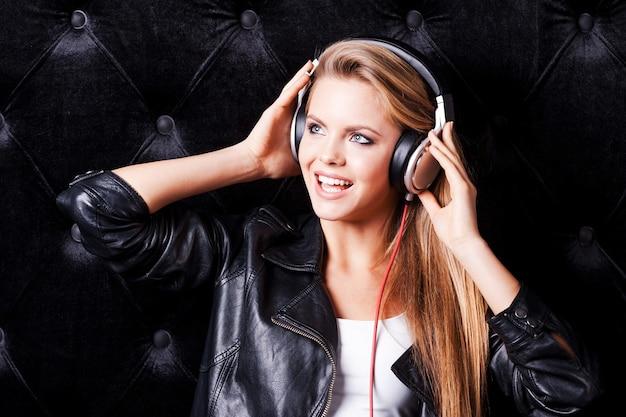 Sie hört ihr lieblingslied. schöne junge frau mit make-up und kopfhörern posiert vor schwarzem hintergrund
