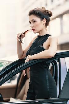 Sie ist bereit, die welt zu gewinnen - selbstbewusste frau, die im dor des autos steht