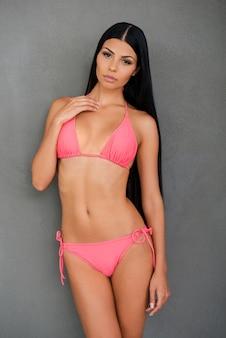 Sie ist stolz auf ihren körper. schöne junge frau im badeanzug, die kamera anschaut, während sie vor grauem hintergrund posiert