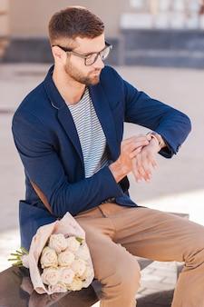 Sie ist wieder zu spät. besorgter junger mann in eleganter jacke, der auf seine uhr schaut, während er auf der bank sitzt, mit einem rosenstrauß in seiner nähe
