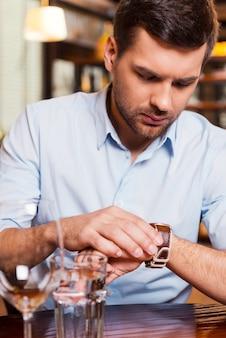 Sie ist wieder zu spät. frustrierter junger mann, der die zeit überprüft, während er im restaurant sitzt?