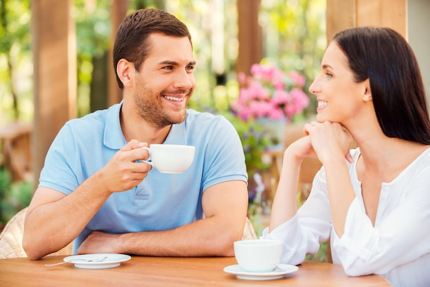 Sie lieben es, zeit miteinander zu verbringen. schönes junges liebevolles paar, das zusammen kaffee im café im freien trinkt