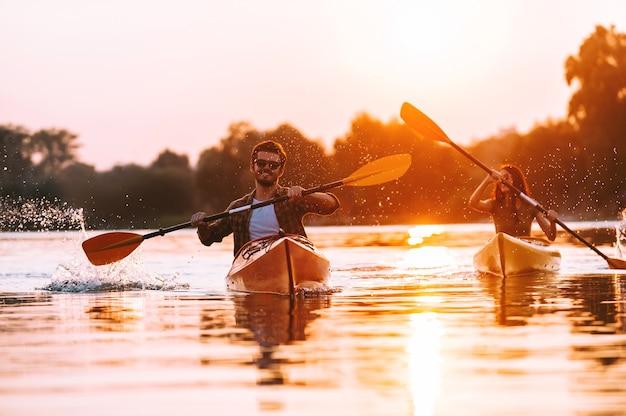 Sie lieben es, zusammen kajak zu fahren. fröhliches junges paar kajakfahren auf dem fluss zusammen mit sonnenuntergang im hintergrund