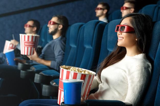 Sie liebt 3d-filme. nette junge frau, die filme 3d aufpassend trägt gläser lacht